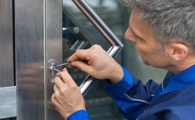 Locksmith working on a door with cylinder lock